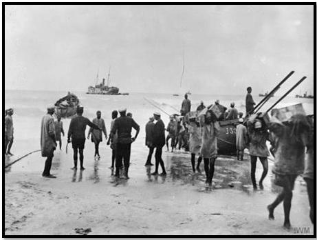 أنفار الفرقة المصرية يقومون بإفراغ إمدادات على شاطئ غزة. ويظهر في الصورة ضباط إنجليز يشرفون على العمل والسياط في أيديهم